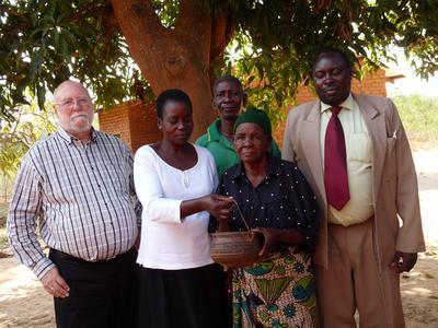 P56990; Brian McNeill, Elizabeth Maland Phiri, Ruth Manda Jazinandi, and Benford Mwakayuni with cooking pot