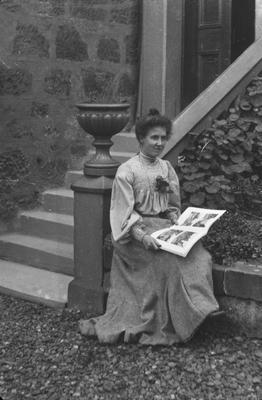 P11663; Edwardian woman in garden with photograph album