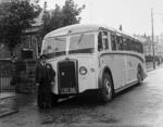 Driver standing beside Fitzcharles bus in Grangemouth