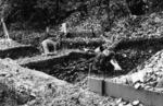 Excavation of shell midden at Inveravon, two people working on excavation.