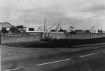 Cars in car park of Nortonwood Alloy Ltd with cranes of MacLellan shipbreakers yard in background.