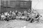 Members of 64 Squadron outside hut at airfield