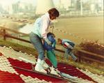 Polmont Ski slope - Woman teaching young child to ski